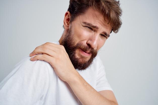 Бородатый мужчина в белой футболке снимает стресс от боли в шее в студии. фото высокого качества