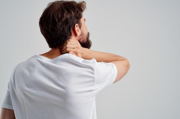Бородатый мужчина в белой футболке стресс медицина боль в шее изолированный фон