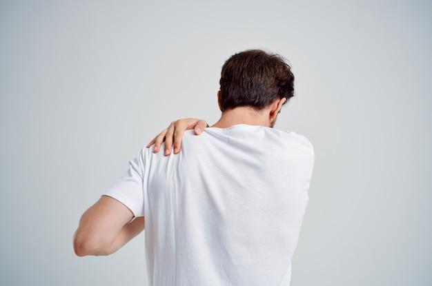 흰색 티셔츠를 입은 수염 난 남자는 목의 밝은 배경에서 약의 통증을 강조합니다