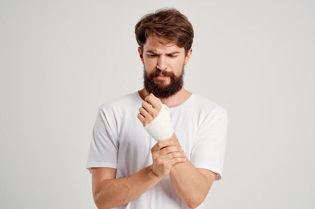 밝은 배경에 붕대를 감은 손으로 흰색 티셔츠를 입은 수염 난 남자