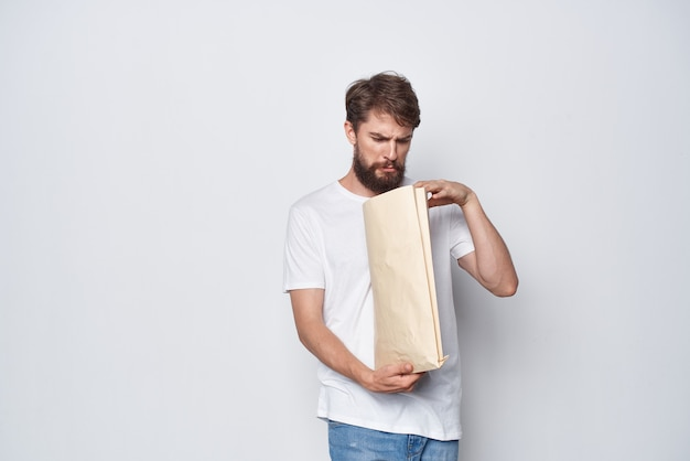 彼の手の感情のモックアップにパッケージを持つ白いtシャツのひげを生やした男