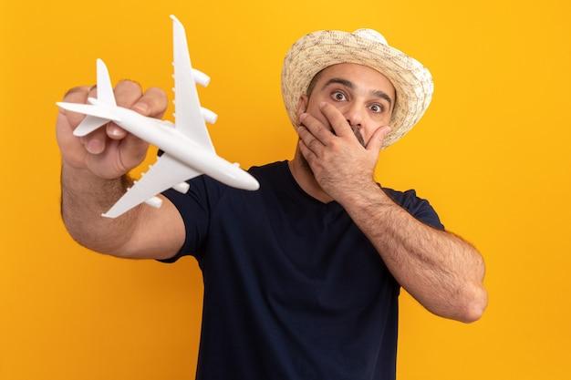 おもちゃの飛行機を持っている黒いtシャツと夏の帽子のひげを生やした男はオレンジ色の壁の上に立っている手で口を覆って驚いて心配しました