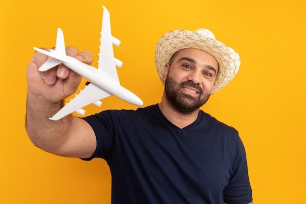검은 티셔츠와 여름 모자에 수염 난 남자 장난감 비행기를 들고 행복하고 긍정적 인 오렌지 벽 위에 유쾌하게 서 웃고