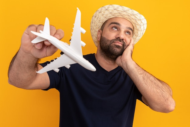 오렌지 벽 위에 의아해 서 찾고 장난감 비행기를 들고 검은 티셔츠와 여름 모자에 수염 난된 남자