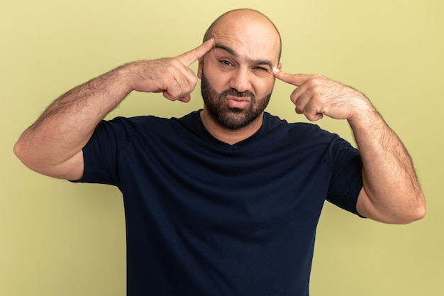 녹색 벽 위에 서있는 그의 사원에서 검지 손가락으로 가리키는 검은 색 티셔츠에 수염 난 남자 짜증과 피곤