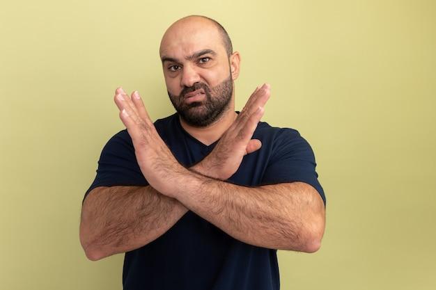 녹색 벽 위에 서있는 손을 crosing 중지 제스처를 만드는 불쾌한 검은 티셔츠에 수염 난 남자