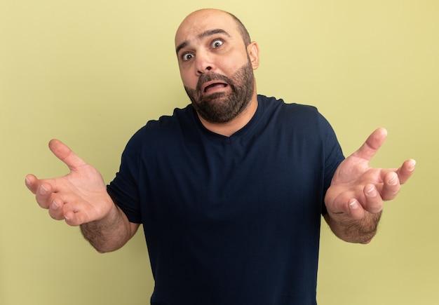 緑の壁の上に立っている腕で混乱し、怖がっている黒いtシャツのひげを生やした男