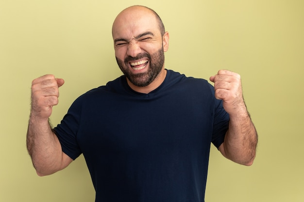 검은 티셔츠에 수염 난 남자 미친 행복하고 흥분된 비명 주먹을 떨림 녹색 벽 위에 서 그의 성공을 기뻐