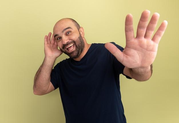 검은 색 티셔츠에 수염 난 남자가 행복하고 녹색 벽 위에 서서 손을 잡고 흥분