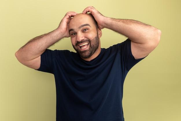 녹색 벽 위에 서있는 그의 머리에 손으로 웃고 행복하고 흥분된 검은 색 티셔츠에 수염 난 남자