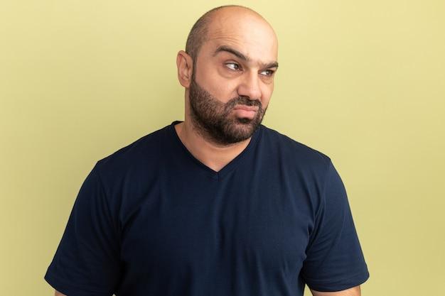 緑の壁の上に立っている怒っている顔で脇を見て黒いtシャツのひげを生やした男
