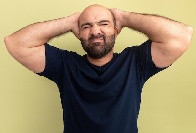 녹색 벽 위에 서있는 그의 머리 뒤에 손으로 혼란스럽고 짜증나는 검은 티셔츠에 수염 난 남자