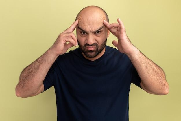 검은 색 티셔츠에 수염 난 남자가 녹색 벽 위에 서있는 강한 두통으로 고통받는 그의 머리를 만지고 짜증이납니다.