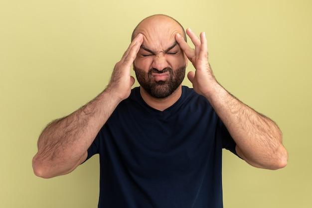 緑の壁の上に立っている強い頭痛に苦しんで彼の頭に触れると気分が悪くてイライラしている黒いtシャツのひげを生やした男