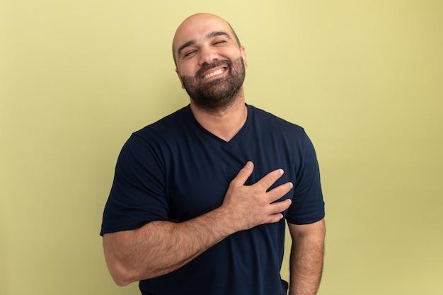 검은 색 티셔츠에 수염 난 남자가 녹색 벽 위에 서있는 고마운 느낌을 그의 chet에 유쾌하게 행복하고 긍정적 인 손을 잡고 웃고