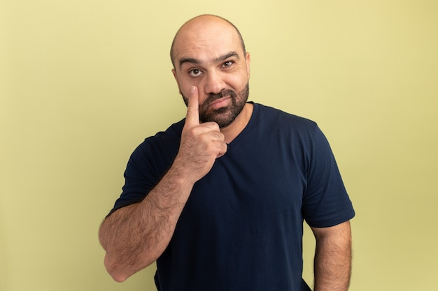 Бородатый мужчина в черной футболке улыбается, указывая указательным пальцем на глаз, стоя над зеленой стеной