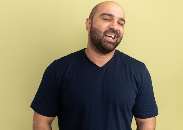 緑の壁の上に立っている幸せそうな顔で笑って黒いtシャツのひげを生やした男