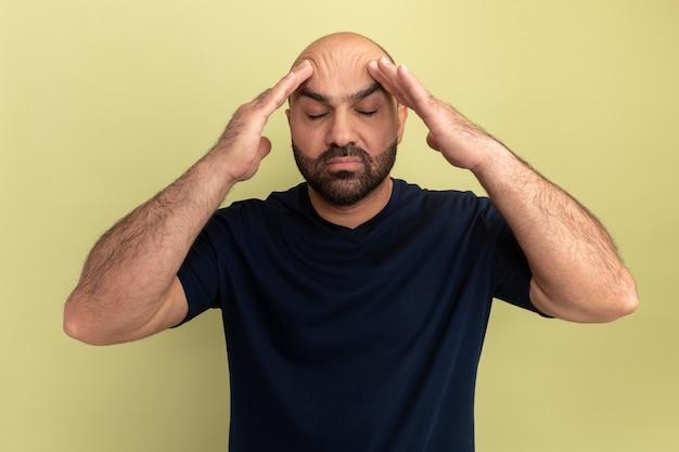 녹색 벽 위에 서있는 두통으로 고통받는 그의 머리를 만지고있는 검은 색 티셔츠에 수염 난 남자