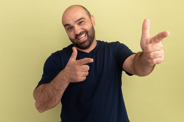 緑の壁の上に立っている人差し指で元気に指している幸せそうな顔と笑顔の黒いtシャツのひげを生やした男