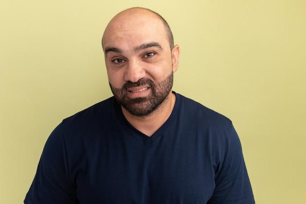 緑の壁の上に立っている顔に笑顔で黒のtシャツのひげを生やした男