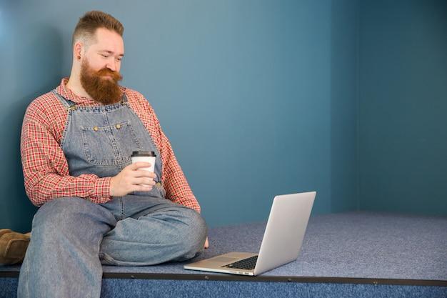 Бородатый мужчина в синем комбинезоне пьет кофе