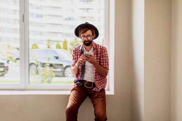 明るい市松模様のシャツを着たひげを生やした男は、スマートフォンデバイスに新しいモバイルアプリケーションをインストールして音楽を聴いています。流行に敏感なスタイル。