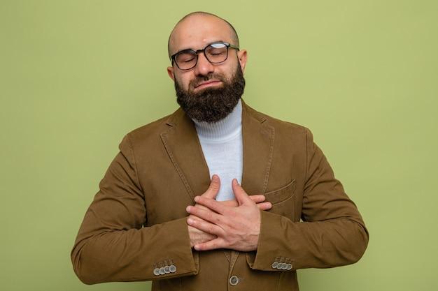 眼鏡をかけている茶色のスーツを着たひげを生やした男は幸せで前向きに胸に手をつないで感謝している