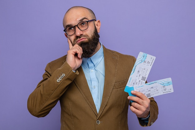 보라색 배경 위에 서 있는 어리둥절한 표정으로 항공권을 들고 안경을 쓴 갈색 양복을 입은 수염 난 남자