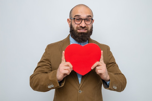 茶色のスーツを着たひげを生やした男は、元気に幸せで前向きな笑顔に見える段ボールから作られたハートを保持している眼鏡をかけています
