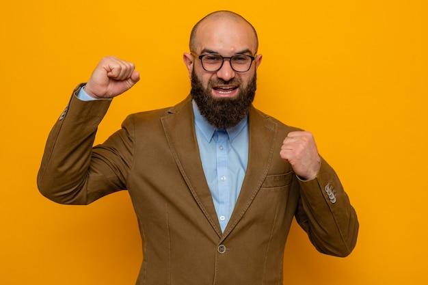 オレンジ色の背景の上に立っている幸せで興奮した握りこぶしをカメラを見て眼鏡をかけて茶色のスーツのひげを生やした男