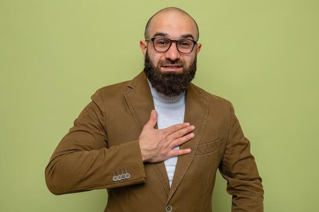 녹색 배경 위에 서 있는 가슴에 손을 잡고 행복하고 긍정적인 미소를 짓고 있는 카메라를 바라보는 안경을 쓴 갈색 양복의 수염 난 남자