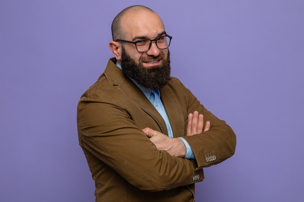 紫色の背景の上に立って腕を組んで幸せでポジティブなカメラを見て眼鏡をかけている茶色のスーツのひげを生やした男