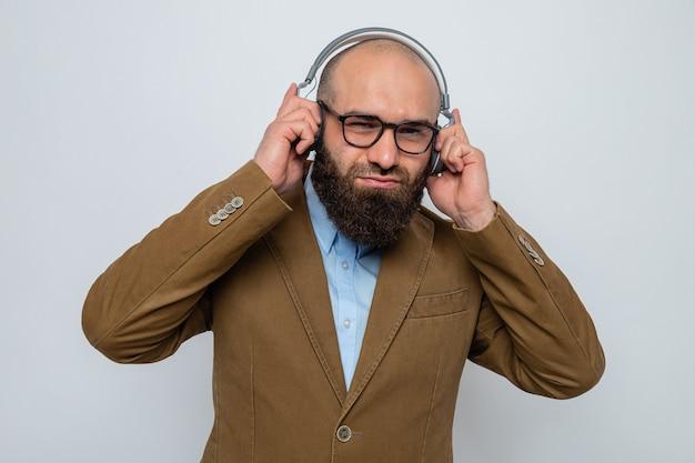 헤드폰을 끼고 안경을 쓰고 음악을 즐기며 웃고 있는 갈색 양복을 입은 수염 난 남자