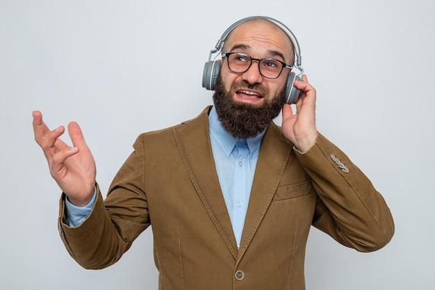헤드폰을 끼고 안경을 쓰고 흰색 배경 위에 서 있는 행복하고 쾌활한 미소를 띤 갈색 정장을 입은 수염 난 남자