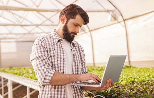 Бородатый мужчина в клетчатой рубашке стоит возле гидропонного стола с зелеными ростками и использует ноутбук для управления автоматическим поливом в современной теплице