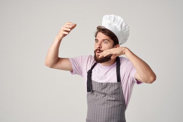 요리사 제복을 입은 수염 난 남자가 손으로 요리 전문가로 몸짓