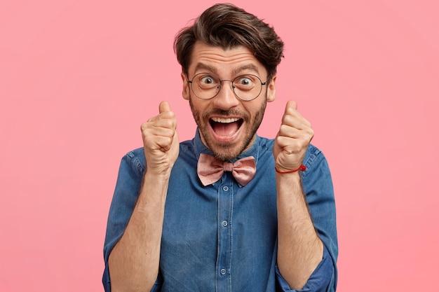 デニムシャツとピンクの蝶ネクタイのひげを生やした男
