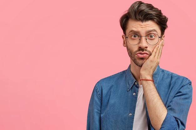 Бородатый мужчина в джинсовой рубашке и круглых очках