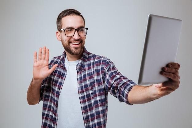 Бородатый мужчина в очках делает селфи на планшетном компьютере
