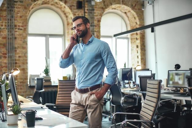 Бородатый мужчина в очках разговаривает по смартфону с клиентом, стоя в современном офисе
