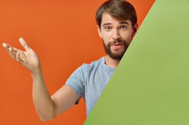 Бородатый мужчина в серой футболке за зеленым плакатом на оранжевой стене.