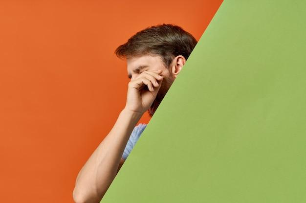 회색 티셔츠 녹색 모형 포스터 오렌지 배경에서 수염 난된 남자