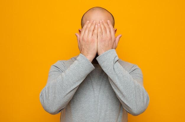オレンジ色の背景の上に立っている手で目を覆う灰色のスウェットシャツのひげを生やした男
