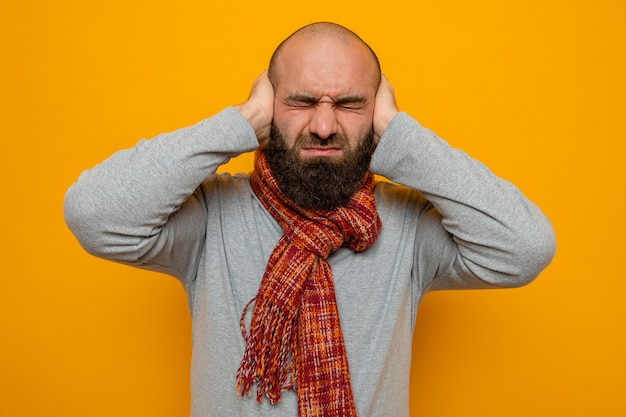 首にスカーフを巻いた灰色のスウェットシャツを着たひげを生やした男が、イライラした表情で耳を手で覆っている