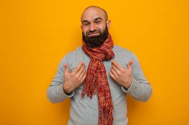 首の周りにスカーフを持った灰色のスウェットシャツを着たひげを生やした男がカメラを見て幸せで前向きな笑顔がオレンジ色の背景の上に立っている自分を元気に指しています