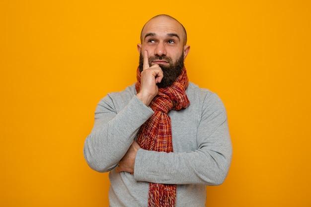 オレンジ色の背景の上に立って夢と笑顔を見上げて首にスカーフと灰色のスウェットシャツのひげを生やした男