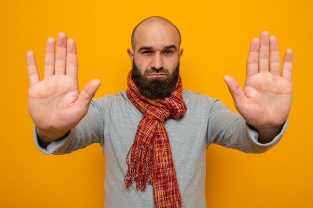 首にスカーフを巻いた灰色のスウェットシャツのひげを生やした男が真面目な顔で見て、手で停止ジェスチャーをしている