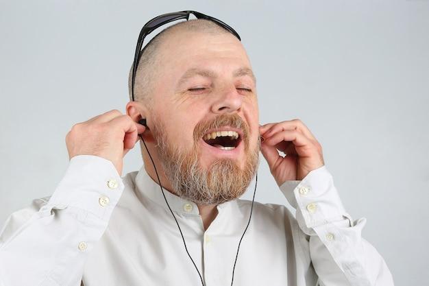 Бородатый мужчина в наушниках слушает музыку