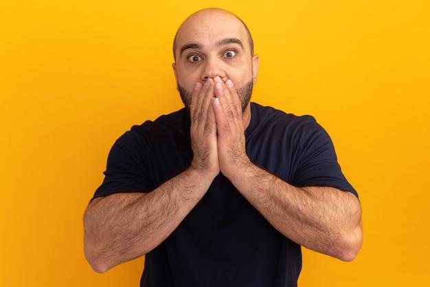해군 티셔츠에 수염 난 남자는 오렌지 벽 위에 서있는 손으로 입을 덮고 놀랐다.