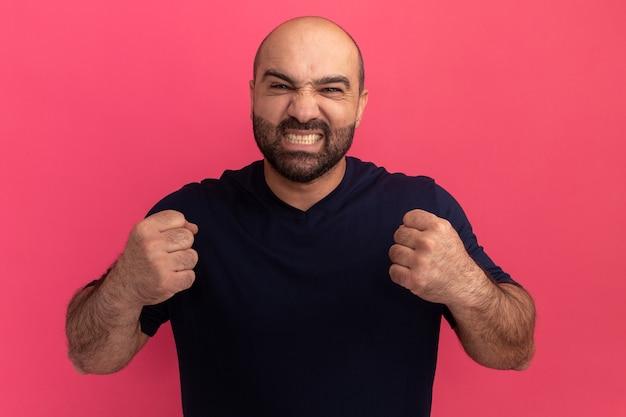 분홍색 벽 위에 서있는 성가신 표정으로 주먹을 떨리는 해군 티셔츠에 수염 난 남자